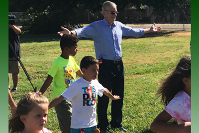 Superintendent Tom Torlakson doing arm stretching exercises together with school children.